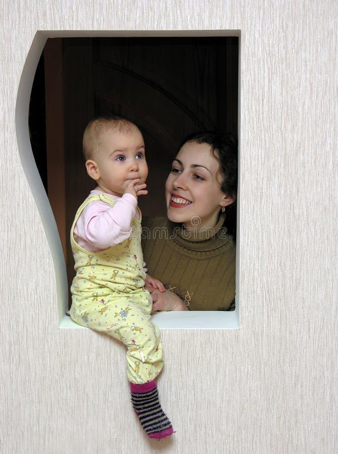 Moeder met baby in venster royalty-vrije stock foto