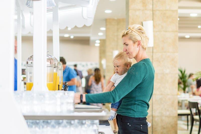 Moeder met babyjongen die van jus d'orange in al inclusief restaurant genieten royalty-vrije stock foto
