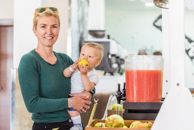 Moeder met babyjongen en appel in al inclusief restaurant stock foto