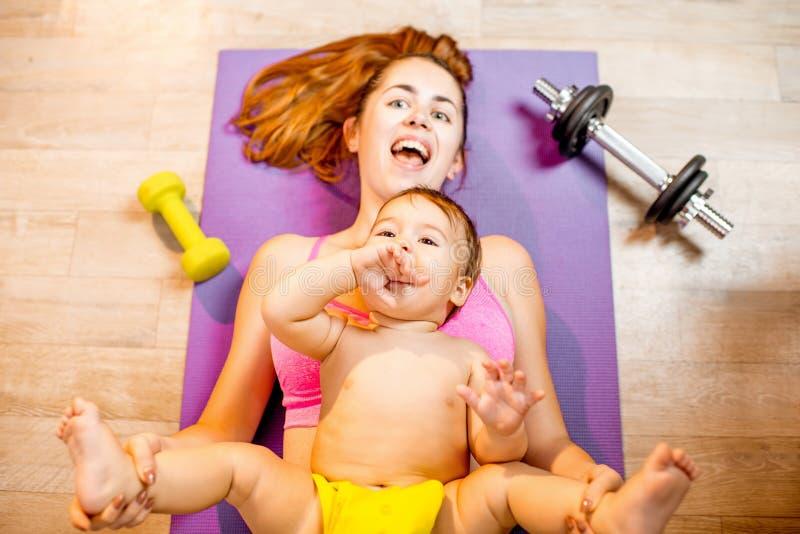 Moeder met babyjongen het uitoefenen op de vloer royalty-vrije stock foto's