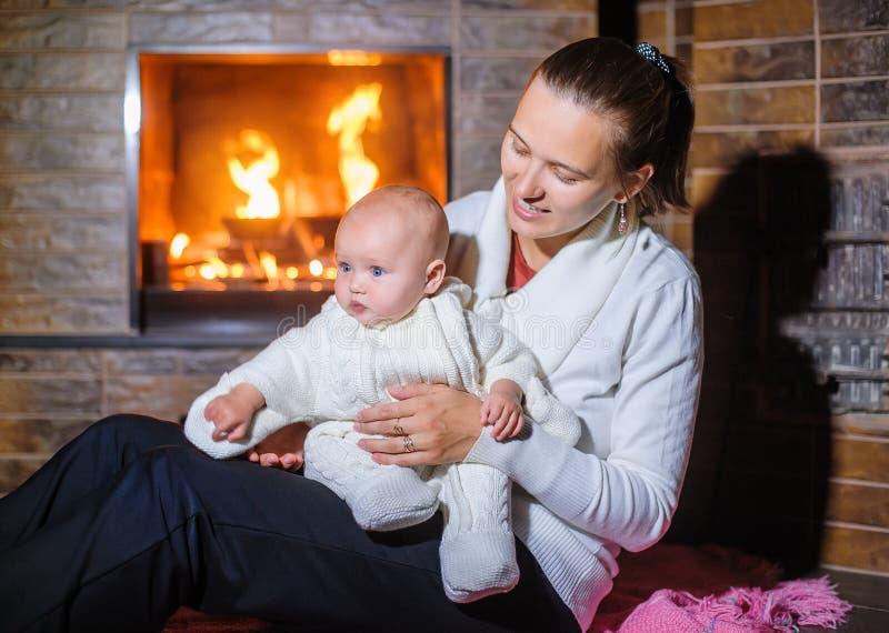 Moeder met babymeisje door de open haard royalty-vrije stock fotografie