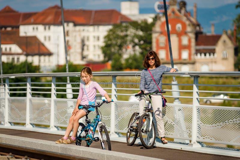 Moeder met daugter die door fietsen in Straatsburg lopen stock afbeeldingen
