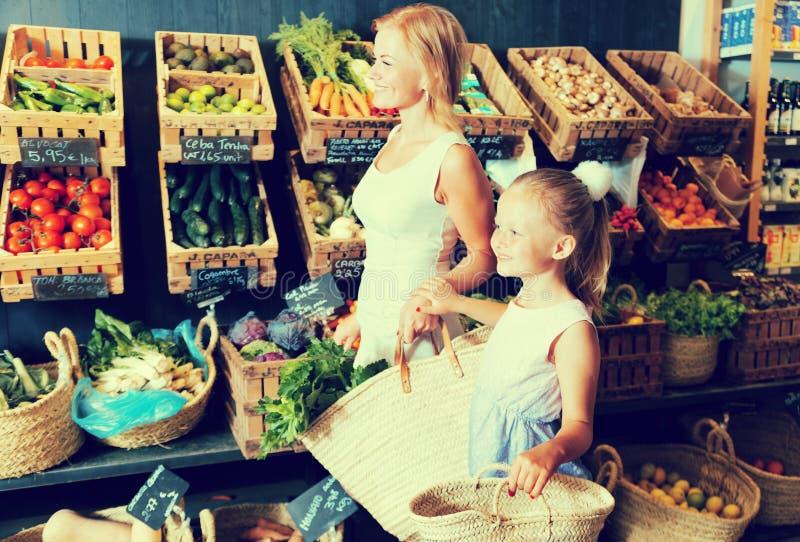 Moeder met dochter die gekoeld voedsel in supermarkt kopen stock afbeeldingen