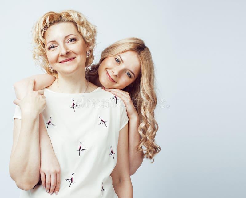 Moeder met dochter die samen het gelukkige glimlachen stellen geïsoleerd op witte achtergrond met copyspace, het concept van leve royalty-vrije stock afbeeldingen