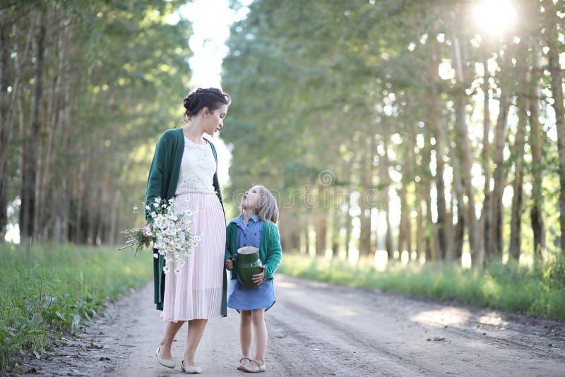 Moeder met dochter het lopen op een weg stock foto's
