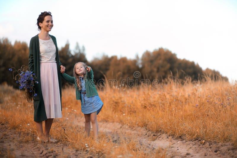 Moeder met dochter het lopen op een weg royalty-vrije stock afbeelding