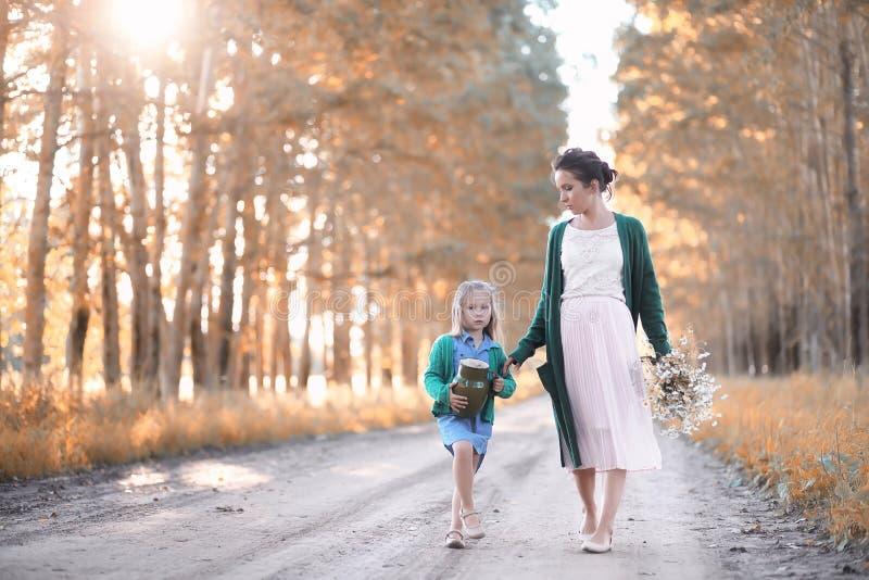 Moeder met dochter het lopen op een weg stock afbeelding