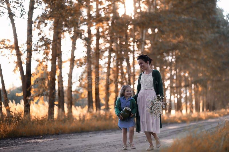 Moeder met dochter het lopen op een weg royalty-vrije stock afbeeldingen