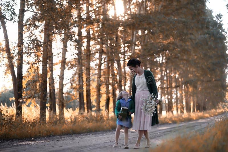 Moeder met dochter het lopen op een weg royalty-vrije stock fotografie