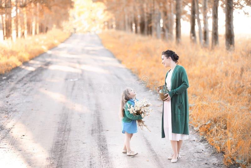 Moeder met dochter het lopen op een weg stock fotografie
