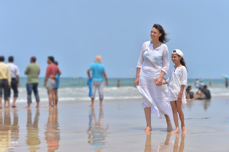 Moeder met dochter het lopen op strand royalty-vrije stock foto's