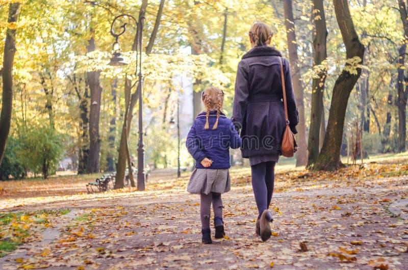Moeder met dochter het lopen in het park in de handen van de de herfstholding stock foto's