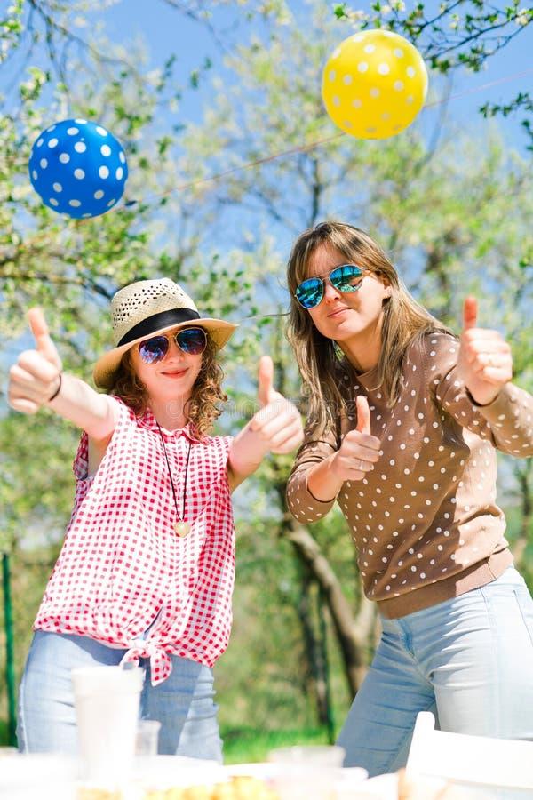 Moeder met dochter op de partij van de verjaardagstuin tijdens de zomer stock fotografie