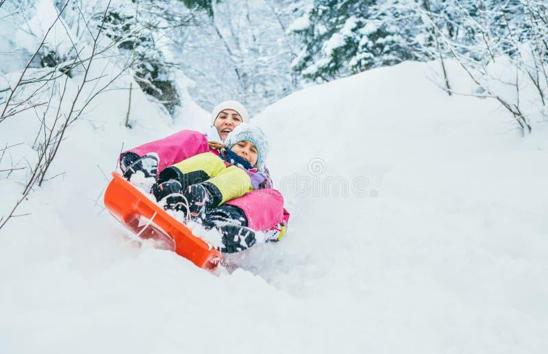 Moeder met dochterdia neer van sneeuwhelling die samen in één dia zitten Het conceptenbeeld van de winteractiviteiten stock afbeelding