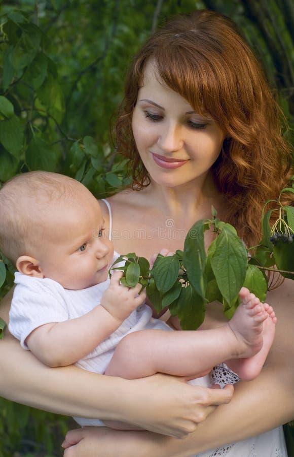moeder met een baby in een tuin royalty-vrije stock afbeelding