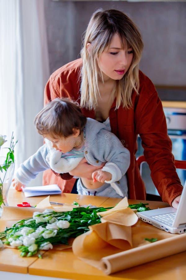 Moeder met een kind die aan het werken als bloemistonderneemster proberen stock foto