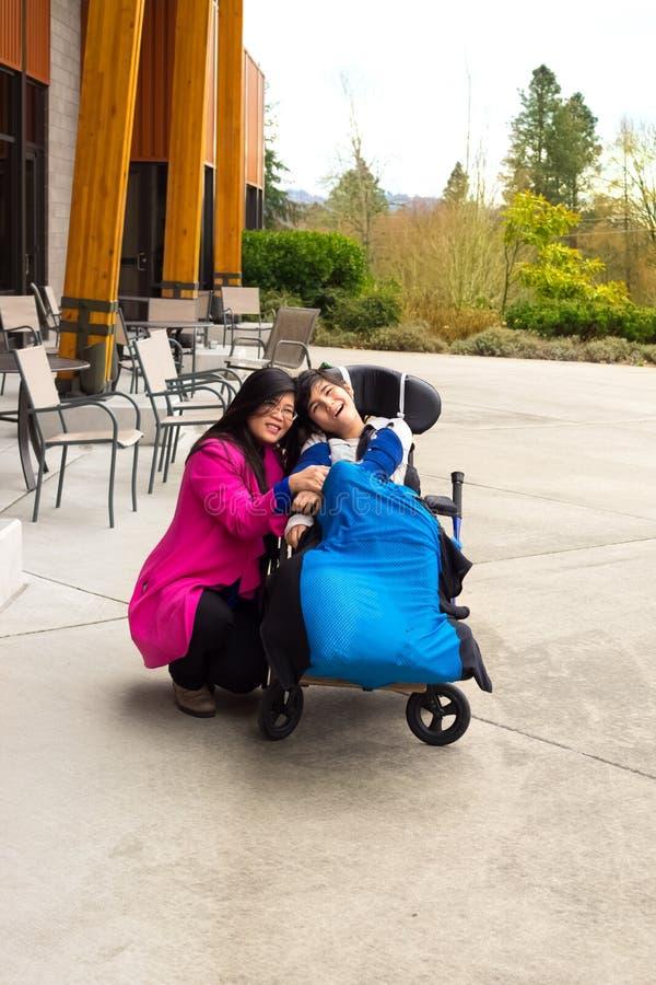 Moeder met gehandicapte elf éénjarigenzoon in rolstoel in openlucht royalty-vrije stock foto's