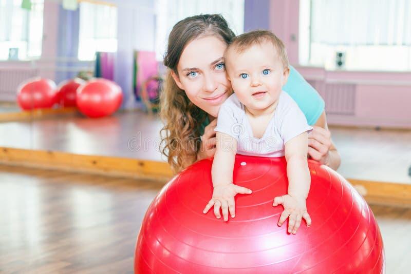 Moeder met gelukkige baby die oefeningen met gymnastiek- bal doen royalty-vrije stock afbeeldingen
