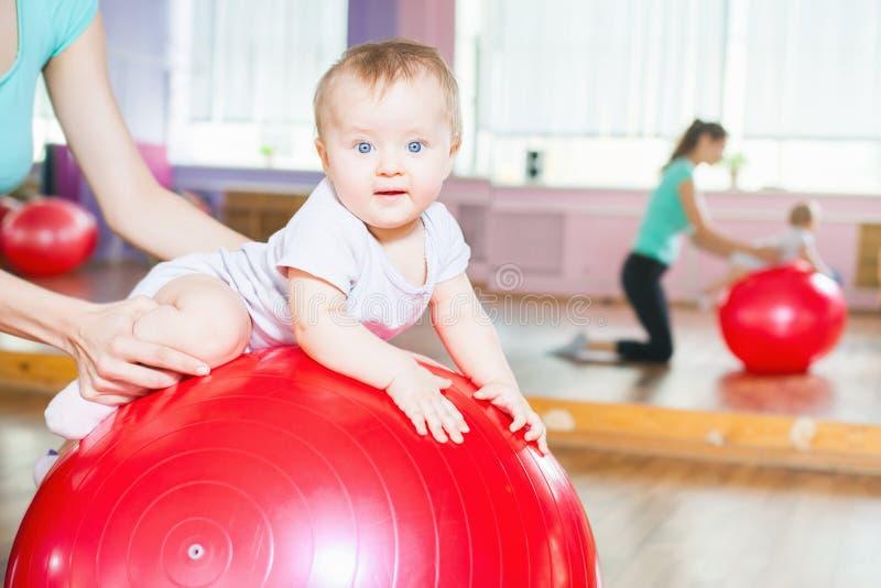 Moeder met gelukkige baby die oefeningen met gymnastiek- bal doen royalty-vrije stock fotografie