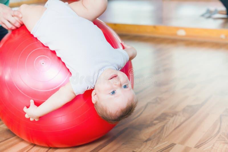 Moeder met gelukkige baby die oefeningen met gymnastiek- bal doen stock afbeelding