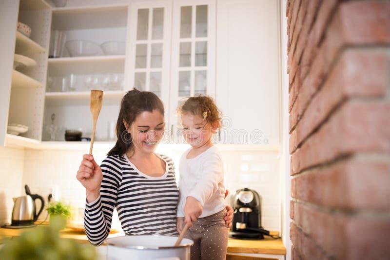 Moeder met haar dochter in de keuken die samen koken stock afbeelding