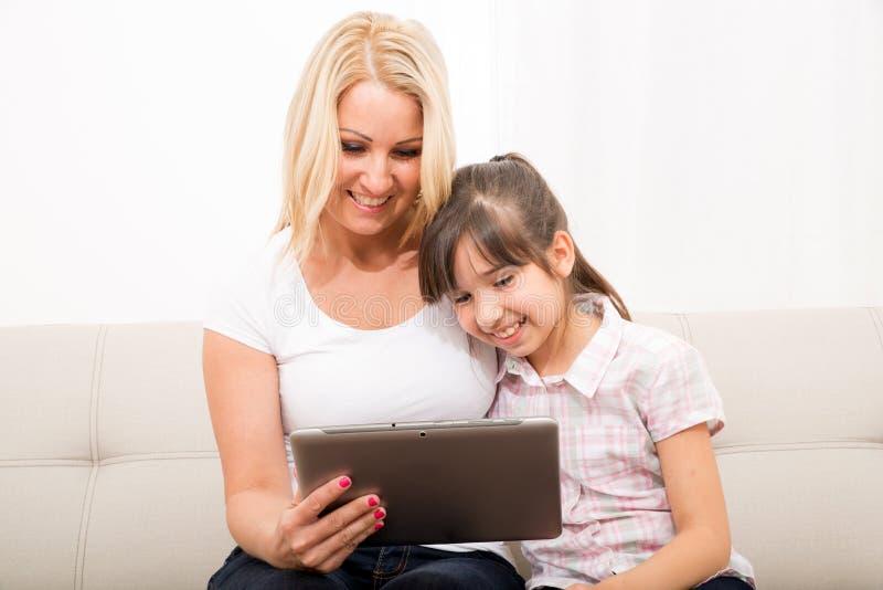 Moeder met haar Dochter die een Tabletpc met behulp van stock fotografie