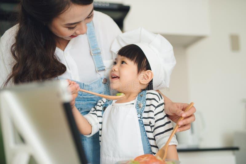Moeder met haar dochter die lunch in de keuken en enjo voorbereiden royalty-vrije stock fotografie