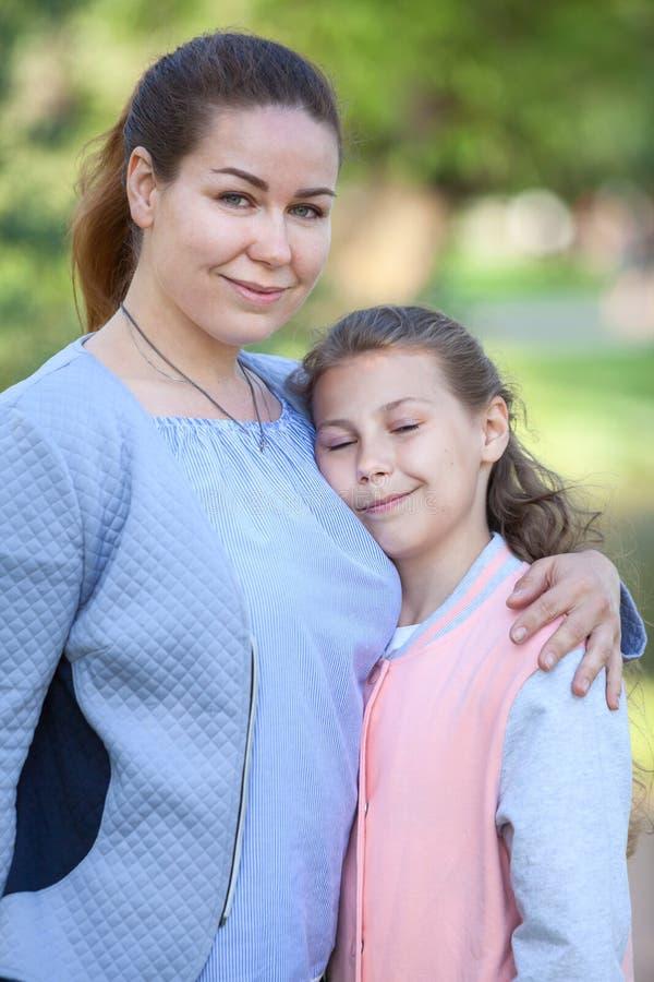 Moeder met haar jonge dochtertribune die, meisje met gesloten ogen omhelzen stock afbeeldingen
