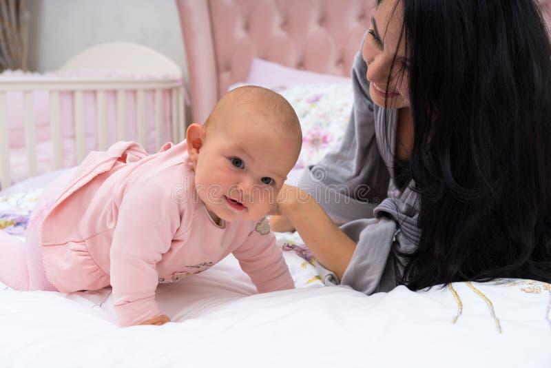 Moeder met haar leuk babymeisje in bed royalty-vrije stock afbeeldingen