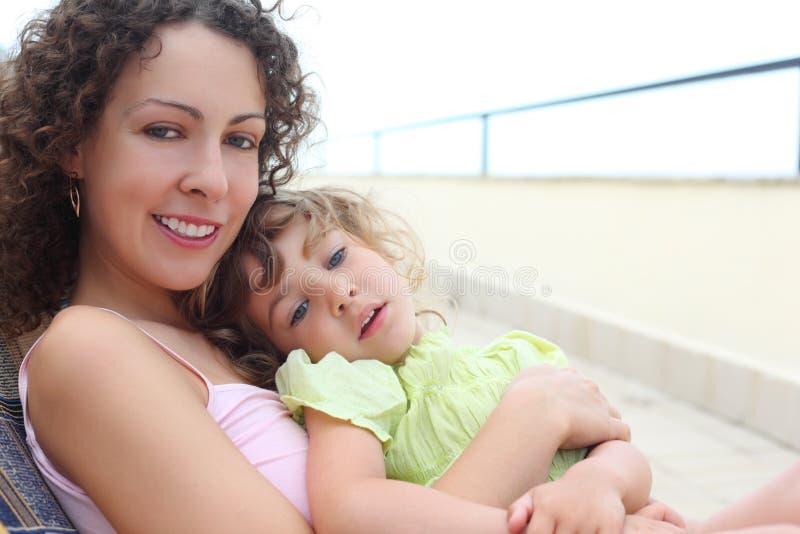 Moeder met kind op veranda stock fotografie