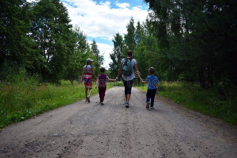 Moeder met kinderen die in het bos lopen stock afbeeldingen
