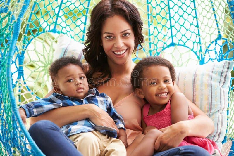 Moeder met Kinderen die op Openluchttuinschommeling Seat ontspannen royalty-vrije stock afbeelding