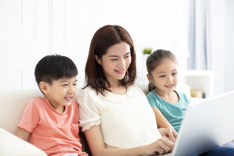 Moeder met kinderen in woonkamer met laptop royalty-vrije stock foto