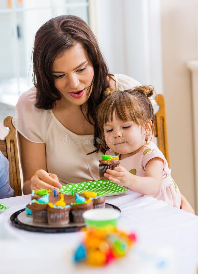 Moeder met Meisje dat Cupcake eet bij Verjaardagspartij royalty-vrije stock afbeelding