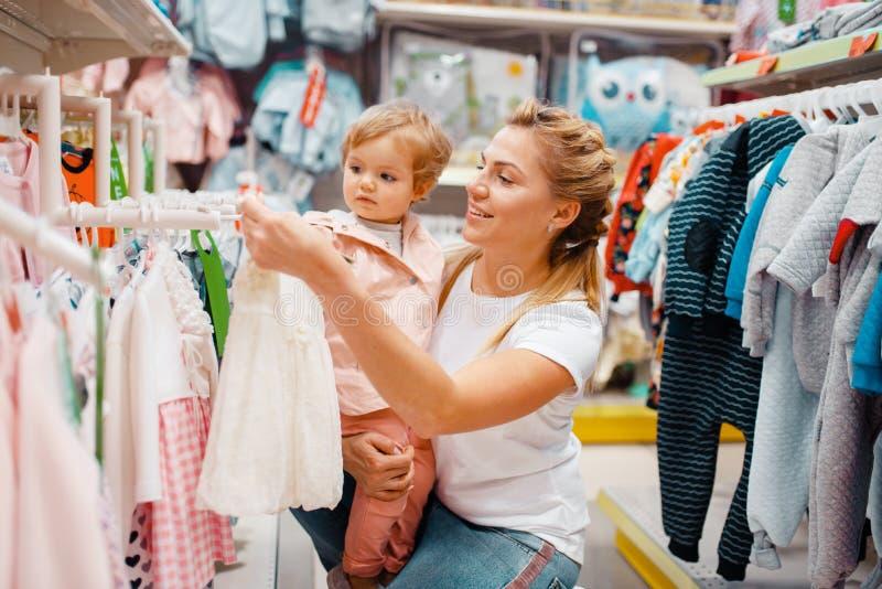Moeder met meisje die kleren in jonge geitjesopslag kiezen royalty-vrije stock foto's