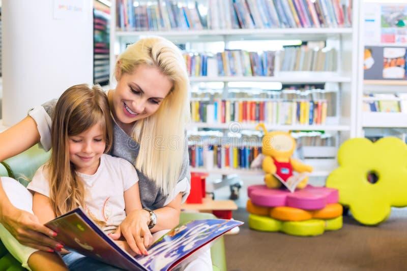Moeder met meisje gelezen boek samen stock fotografie