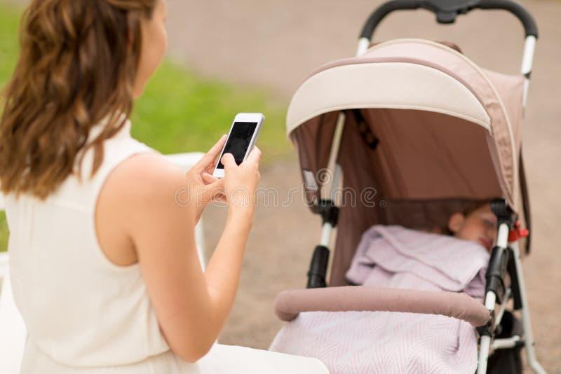 Moeder met smartphone en baby in wandelwagen stock afbeeldingen