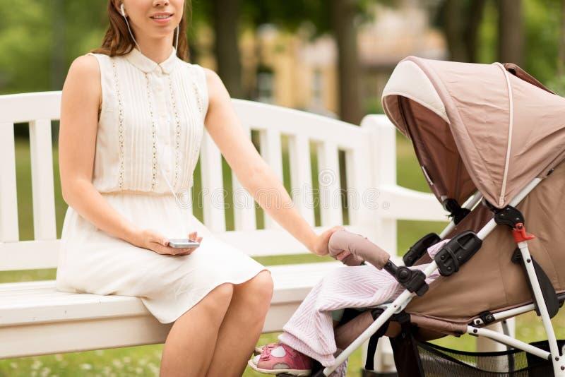 Moeder met smartphone, oortelefoons en wandelwagen royalty-vrije stock foto's