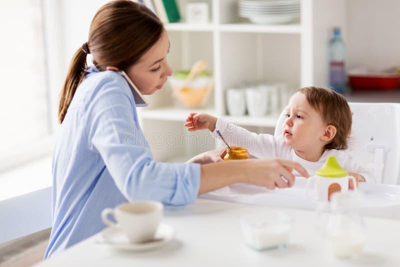 Moeder met smartphone voedende baby thuis stock foto's