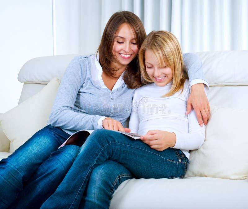 Moeder met Tiener de lezingsTijdschrift van de Dochter stock afbeelding
