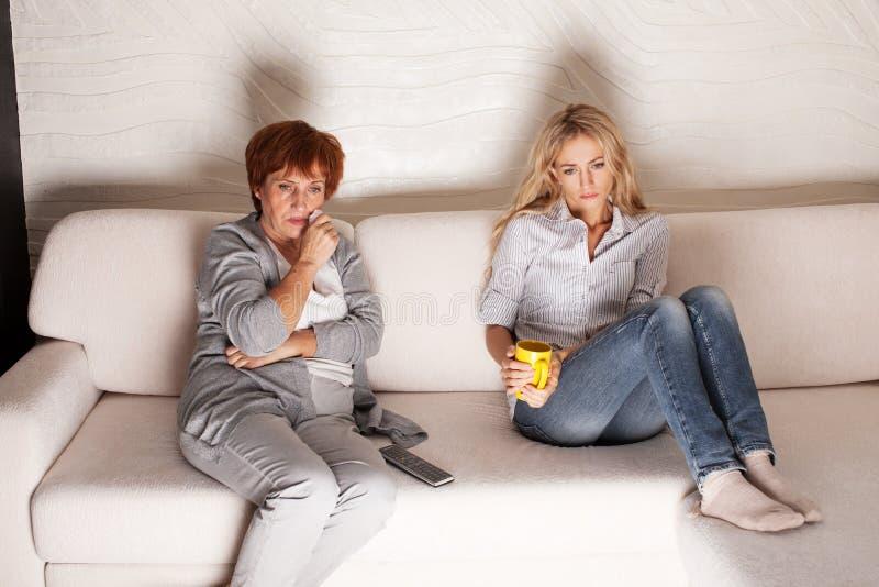 Moeder met volwassen dochter die op TV letten stock foto
