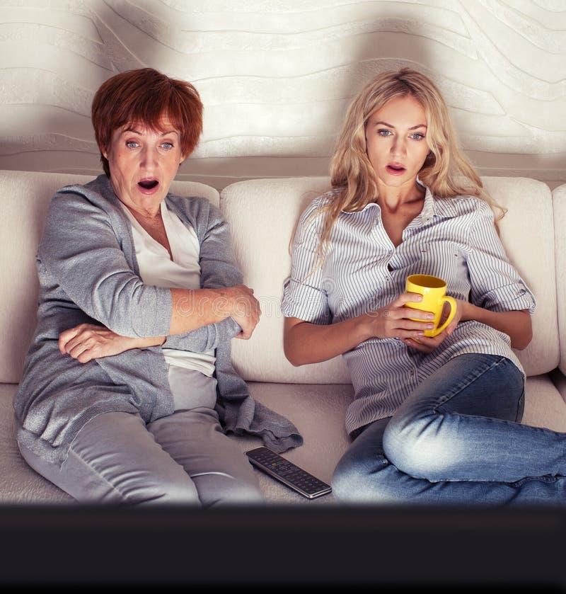 Moeder met volwassen dochter het letten op televisie stock afbeelding