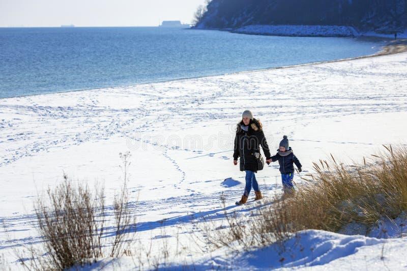 Moeder met weinig zoon die op sneeuwstrand lopen royalty-vrije stock foto's