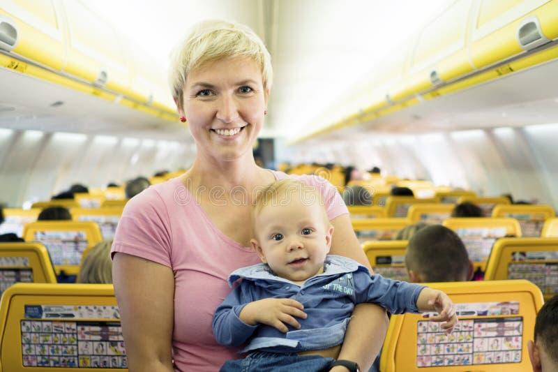 Moeder met zes van de babymaanden oud jongen in het vliegtuig stock foto's
