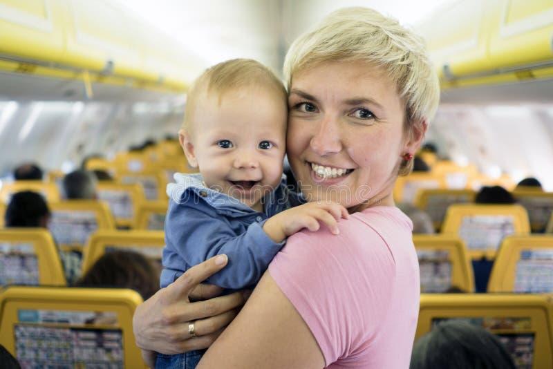 Moeder met zes van de babymaanden oud jongen in het vliegtuig royalty-vrije stock afbeeldingen