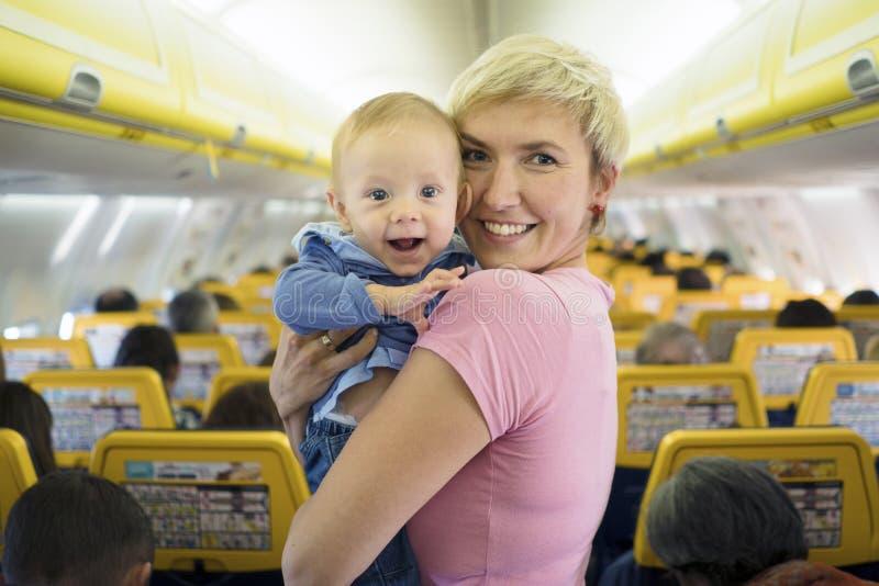 Moeder met zes van de babymaanden oud jongen in het vliegtuig stock foto