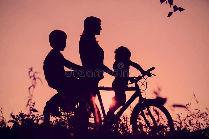 Moeder met zoon en dochter berijdende fiets bij zonsondergang royalty-vrije stock afbeeldingen