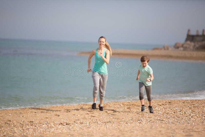 Moeder met zoon het lopen op het strand stock fotografie