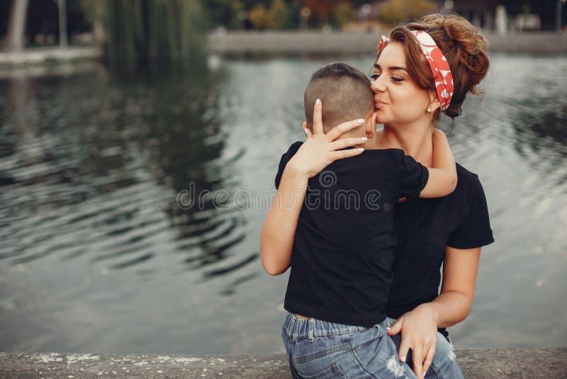 Moeder met zoon het spelen in een de zomerpark stock afbeelding