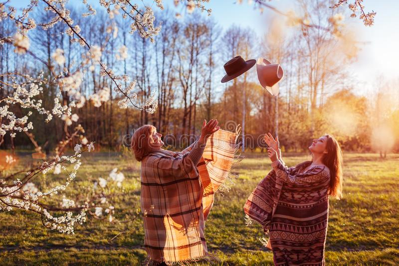 Moeder op middelbare leeftijd en haar volwassen dochter die hoeden in bloeiende tuin werpen De dagconcept van de moeder ` s Vrouw royalty-vrije stock foto's
